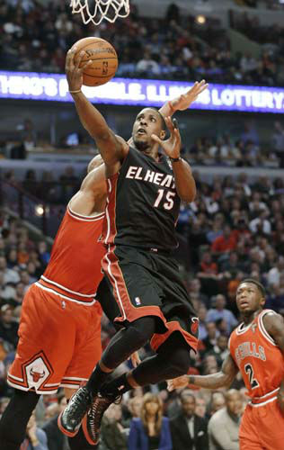 Miami Heat guard Mario Chalmers &#40;15&#41; drives to the basket past Chicago Bulls forward Carlos Boozer during the first half of an NBA basketball game in Chicago on Wednesday, March 27, 2013. &#40;AP Photo&#47;Nam Y. Huh&#41; <span class=meta>(AP Photo&#47; Nam Y. Huh)</span>