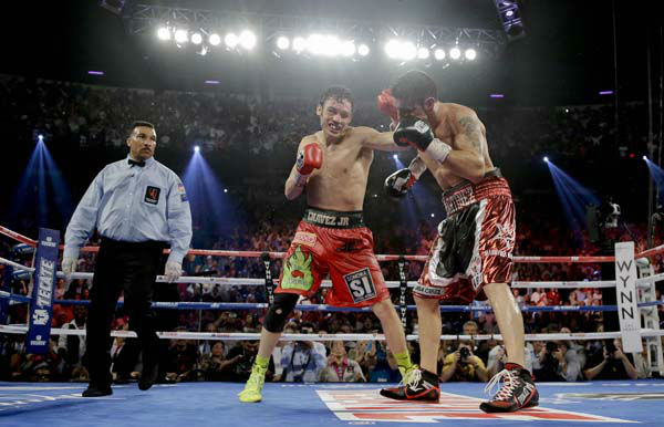 Julio Cesar Chavez Jr., center, lands a punch against Sergio Martinez in the 12th round as referee Tony Weeks, left, looks on during the WBC middleweight title fight, Saturday, Sept. 15, 2012, in Las Vegas. Martinez won by unanimous decision. &#40;AP Photo&#47;Julie Jacobson&#41; <span class=meta>(AP Photo&#47; Julie Jacobson)</span>