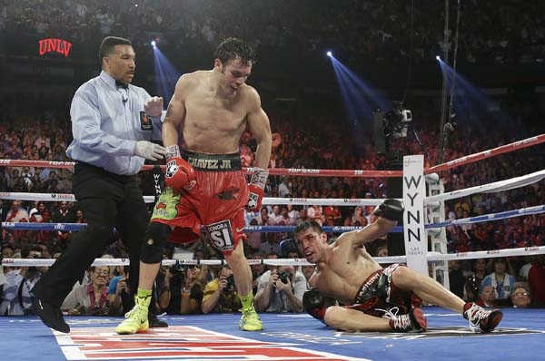 Julio Cesar Chavez Jr., center, looks down at Sergio Martinez after knocking him down for the second time in the 12th round during the WBC middleweight title fight, Saturday, Sept. 15, 2012, in Las Vegas. Martinez won by unanimous decision. &#40;AP Photo&#47;Julie Jacobson&#41; <span class=meta>(AP Photo&#47; Julie Jacobson)</span>