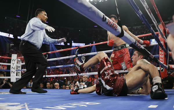 Sergio Martinez falls to the mat as referee Tony Weeks directs Julio Cesar Chavez Jr. to his corner in the 12th round during the WBC middleweight title fight, Saturday, Sept. 15, 2012, in Las Vegas. Martinez won by unanimous decision. &#40;AP Photo&#47;Julie Jacobson&#41; <span class=meta>(AP Photo&#47; Julie Jacobson)</span>