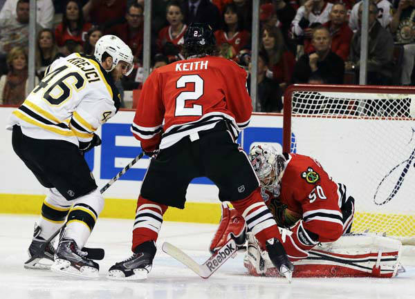 Chicago Blackhawks goalie Corey Crawford &#40;50&#41; saves a shot by Boston Bruins center David Krejci &#40;46&#41; as Blackhawks defenseman Duncan Keith &#40;2&#41; watches during the first period of Game 1 in their NHL Stanley Cup Final hockey series, Wednesday, June 12, 2013, in Chicago. &#40;AP Photo&#47;Nam Y. Huh&#41; <span class=meta>(AP Photo&#47; Nam Y. Huh)</span>