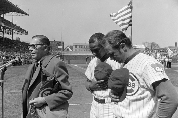Milton Berle leads opening-day crowd in prayer for safe return of Apollo 13 astronauts Tuesday, April 14, 1970 in Chicago. Cubs played Philadelphia before a capacity crowd in Chicago. (AP Photo)Chicago Cubs co-captains Ernie Banks and Ron Santo, right, bow heads as master of ceremonies