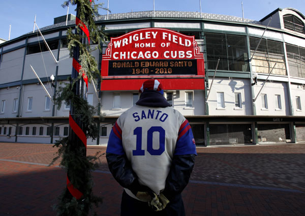 Chicago Cubs' fan Marvin Perez Sr. wears a Ron Santo jacket in front of the Wrigley Field marquee as the news of Santo's death was announced Friday, Dec. 3, 2010, in Chicago. (AP Photo/Charles Rex Arbogast)