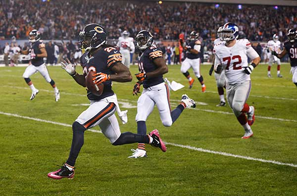 Chicago Bears cornerback Tim Jennings (26) runs for a touchdown after intercepting a pass by New York Giants quarterback Eli Manning in the first half of an NFL football game, Thursday, Oct. 10, 2013, in Chicago. (AP Photo/Charles Rex Arbogast)
