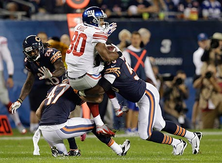 New York Giants wide receiver Victor Cruz (80) is tackled by Chicago Bears safety Chris Conte (47) and linebacker James Anderson (50) in the first half of an NFL football game, Thursday, Oct. 10, 2013, in Chicago. (AP Photo/Nam Y. Huh)