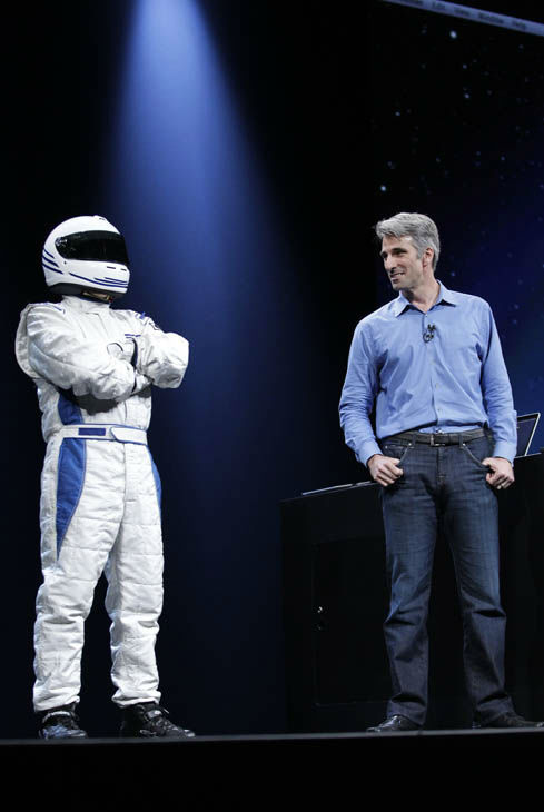 Apple&#39;s Craig Federighi, right, stands next to a man in a racer outfit that talks about the games for the new Mountain Lion for Macs at the Apple Developers Conference in San Francisco, Monday, June 11, 2012. The new Mountain Lion system narrows the gap between the PC and phone software packages, making Mac personal computers work more like iPhones.  &#40;AP Photo&#47;Paul Sakuma&#41; <span class=meta>(AP Photo&#47; Paul Sakuma)</span>