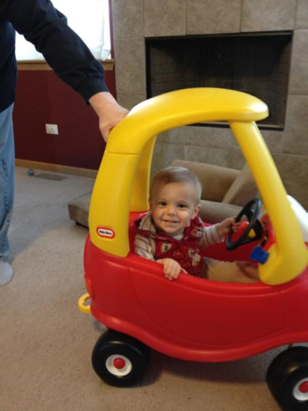 Jaxsen Brockman 14 mos old  His first car....a cozy coupe, he got it for his first birthday. He loves nice days when he gets to ride in it.