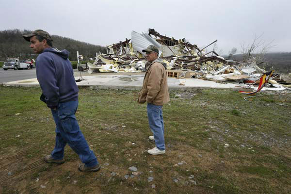 Larry Gammill, left, who attends Botkinburg Foursquare Church, and his friend Tim Parks walk from what is left of the church in Botkinburg, Ark., Thursday, April 11, 2013 after a severe storm struck the building late Wednesday. The National Weather Service is surveying areas Thursday to determine whether tornadoes or strong winds caused damage. &#40;AP Photo&#47;Danny Johnston&#41; <span class=meta>(AP Photo&#47; Danny Johnston)</span>