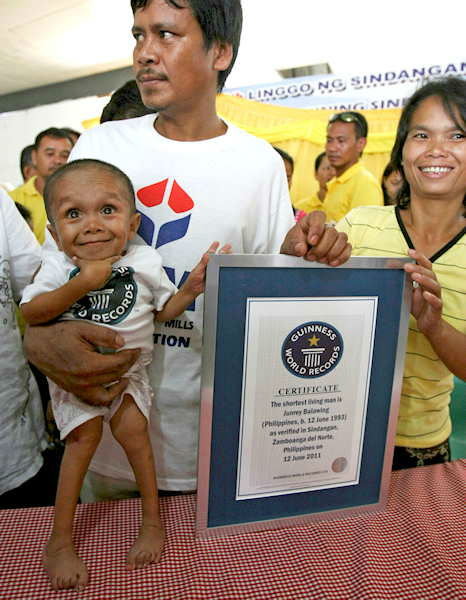 Junrey Balawing smiles as he poses with his Guinness World Records certificate declaring him the world&#39;s shortest living man following the last of a series of measurements conducted at Sindangan Municipal Hall, Sindangan township, Zamboanga Del Norte province in Southern Philippines, Sunday June 12, 2011, his 18th birthday and coincidentally the Philippines&#39; Independence Day. Balawing was officially measured at at 23.5 inches &#40;59.93 centimeters&#41; dislodging Nepal&#39;s Khagendra Thapa Magar with a measurement of 26.4 inches. Holding him is his father Reynaldo and his mother Concepcion at right. <span class=meta>(Photo&#47;AP)</span>