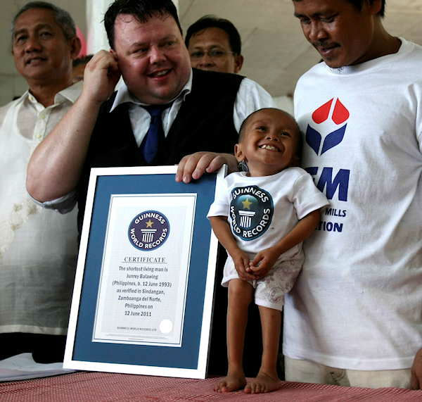 Junrey Balawing smiles as he is presented by Craig Glenday, second from left, with a Guinness World Records certificate for being the world&#39;s shortest living man following the last of a series of measurement conducted at Sindangan Municipal Hall, Sindangan township, Zamboanga Del Norte province in Southern Philippines, Sunday June 12, 2011, his 18th birthday and coincidentally the Philippines&#39; Independence Day. Balawing was officially measured at at 59.93 Centimeters &#40;23.5 inches&#41; dislodging Nepal&#39;s Khagendra Thapa Magar with a measurement of 26.4 inches. At left is Sindangan Mayor Filomeno Sy, and at right is Balawing&#39;s father Reynaldo.  <span class=meta>(Photo&#47;AP)</span>