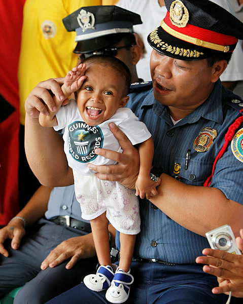 Junrey Balawing is helped by a police officer to make a salute during celebration of the Philippines&#39; ndependence at Sindangan Municipal Hall, Sindangan township, Zamboanga Del Norte province in Southern Philippines, Sunday June 12, 2011, his 18th birthday. Balawing was officially declared &#34;the world&#39;s shortest living man&#34; with a measurement of 23.5 inches &#40;59.93 centimeters&#41; dislodging Nepal&#39;s Khagendra Thapa Magar with a measurement of 26.4 inches.  <span class=meta>(Photo&#47;AP)</span>