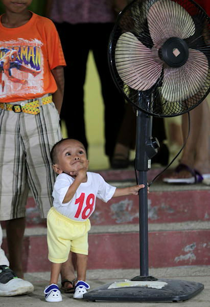 Junrey Balawing holds into an electric fan after being measured by a Guinness World Records representative at Sindangan Health Center, Sindangan township, Zamboanga Del Norte province in Southern Philippines Saturday June 11, 2011, the eve of his 18th birthday which is coincidentally the Philippines Independence Day. Officials said Saturday Balawing was measured at 24 and 1&#47;4 inches &#40;about 61 centimeters&#41; lying down and about two inches shorter than the current record holder Khagendra Thapa Magar of Nepal and is expected to be officially named as the world&#39;s shortest living man when he turns 18 Sunday. <span class=meta>(Photo&#47;AP)</span>