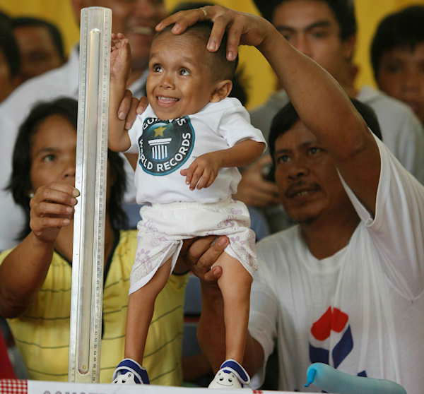 "<div class=""meta ""><span class=""caption-text "">Junrey Balawing, 18, smiles as he stands next to a ruler being held by his mother Concepcion prior to the last of a series of measurements conducted by Guinness World Records at Sindangan Municipal Hall in Sindangan township, Zamboanga Del Norte province in Southern Philippines, Sunday June 12, 2011. Balawing was officially declared 'the world's shortest living man' with a measurement of 59.93 Centimeters (23.5 inches) dislodging Nepal's Khagendra Thapa Magar with a measurement of 26.4 inches. At right is Junrey's father Reynaldo.  (Photo/AP)</span></div>"