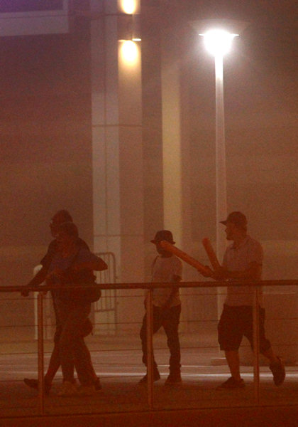 People walk in downtown Phoenix during a dust storm Tuesday, July 5, 2011. A massive dust storm has swept into the Phoenix area and drastically reduced visibility across much of the valley. <span class=meta>(AP Photo&#47;Ross D. Franklin)</span>