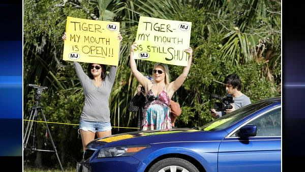Victoria Martin, left, and Meredith Walusek hold up signs outside one of the entrances to Sawgrass Players Club Friday, Feb. 19, 2010, in Ponte Vedra Beach, Fla. The two women were part of a radio station promotion.