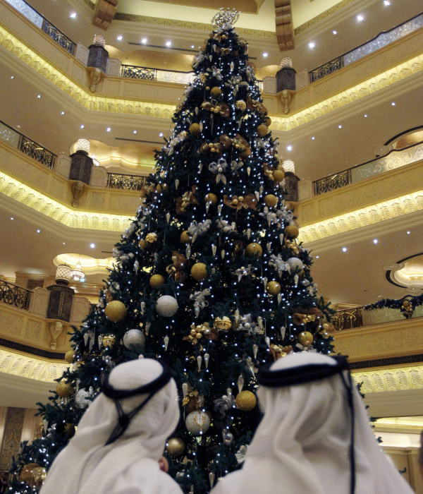 Two Emirate men look to a Christmas tree which has been decked out with dollars 11 million U.S. &#40;14.3 million euro&#41; worth of gold, at the Emirates Palace hotel, in Abu Dhabi, United Arab Emirates, on Thursday Dec. 16, 2010. The hotel&#39;s general manager, Hans Olbertz, was quoted in local newspapers Thursday as saying the 43-foot &#40;13-meter&#41; faux fir has 131 ornaments that include gold and precious stones including diamonds and sapphires. The &#36;11 million symbol of the season has become the latest extravagance at the Emirates Palace hotel, which boasts its own marina, heliport and a vending machine that pops out small gold bars.  <span class=meta>(AP Photo)</span>