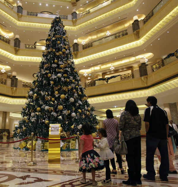 Tourists view the Christmas tree which has been decked out with dollars 11 million U.S. &#40;14.3 million euro&#41; worth of gold, at the Emirates Palace hotel, in Abu Dhabi, United Arab Emirates, on Thursday Dec. 16, 2010. The hotel&#39;s general manager, Hans Olbertz, was quoted in local newspapers Thursday as saying the 43-foot &#40;13-meter&#41; faux fir has 131 ornaments that include gold and precious stones including diamonds and sapphires. The &#36;11 million symbol of the season has become the latest extravagance at the Emirates Palace hotel, which boasts its own marina, heliport and a vending machine that pops out small gold bars. <span class=meta>(AP Photo)</span>