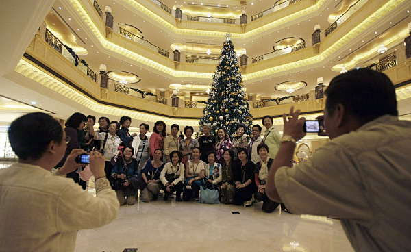 Tourists pose to have their photos taken in front of a Christmas tree which has been decked out with dollars 11 million U.S. &#40;14.3 million euro&#41; worth of gold, at the Emirates Palace hotel, in Abu Dhabi, United Arab Emirates, on Thursday Dec. 16, 2010. The hotel&#39;s general manager, Hans Olbertz, was quoted in local newspapers Thursday as saying the 43-foot &#40;13-meter&#41; faux fir has 131 ornaments that include gold and precious stones including diamonds and sapphires. The &#36;11 million symbol of the season has become the latest extravagance at the Emirates Palace hotel, which boasts its own marina, heliport and a vending machine that pops out small gold bars. <span class=meta>(AP Photo)</span>