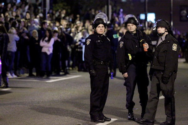 Police officers watch over students rallying in support of Penn State coach Joe Paterno off campus, Tuesday, Nov. 8, 2011, in State College, Pa. (AP Photo/Matt Rourke)