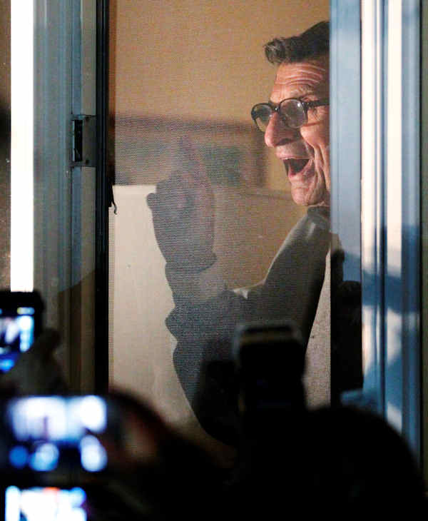 "Penn State football coach Joe Paterno address supporters from a window at his home, Tuesday, Nov. 8, 2011, in State College, Pa. Paterno's support among the Penn State board of trustees was described as ""eroding"" Tuesday, threatening to end the 84-year-old coach's career amid a child sex-abuse scandal involving a former assistant and one-time heir apparent. (AP Photo/Matt Rourke)"
