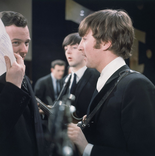 "John Lennon of the Beatles is shown backstage speaking with manager Brian Epstein at the ""Ed Sullivan Show"" in New York, Feb. 1964. In the background is basist Paul McCartney. (AP Photo)"
