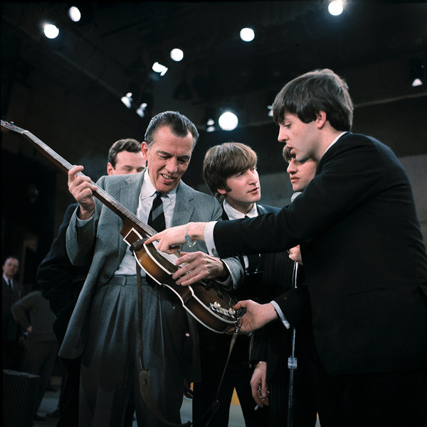 "Paul McCartney, right, shows his guitar to Ed Sullivan before the Beatles' live television appearance on ""The Ed Sullivan Show"" in New York City, Feb. 9, 1964. In the center are, John Lennon, left, and Ringo Starr, partial view. (AP Photo)"