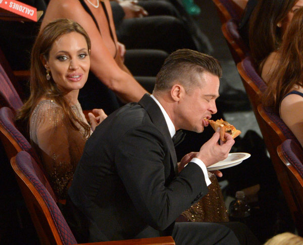 Brad Pitt, foreground, eats pizza as Angelina Jolie, looks on in the audience during the Oscars at the Dolby Theatre on Sunday, March 2, 2014, in Los Angeles. (Photo by John Shearer/Invision/AP)