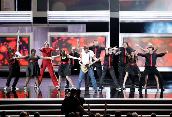 Jimmy Fallon performs the opening number during the 62nd Primetime Emmy Awards Sunday, Aug. 29, 2010, in Los Angeles. Performing with Fallon are Randy Jackson, far left, the cast of Glee, Tna Fey, fourth left, Jorge Garcia, third right, and John Hamm, far right. (AP Photo/Chris Carlson)
