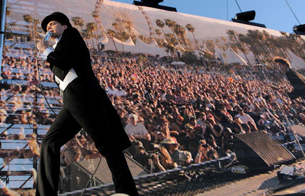 The Hives is one of the many artists taking the stage at the first Budweiser Made in America music festival. The two-day music festival will be stretched across three stages on the Benjamin Franklin Parkway in Philadelphia's Fairmount Park on Saturday, September 1, and Sunday, September 2. Pictured: Pelle Almqvist of The Hives walks past a video monitor showing the crowd during their performance at the first weekend of the 2012 Coachella Valley Music and Arts Festival, Sunday, April 15, 2012, in Indio, Calif. (AP Photo/Chris Pizzello)