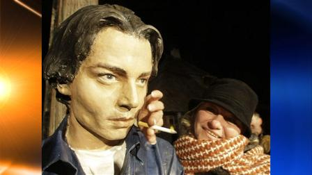 A woman poses with the bust of U.S. actor Johnny Depp in the village of Drvengrad, at Mt. Mokra Gora, in south Serbia, Wednesday, Jan. 13, 2010.