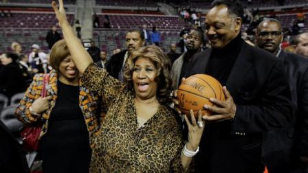 Aretha Franklin walks on the court with Jesse Jackson after the Detroit Pistons-Miami Heat NBA basketball game in Auburn Hills, Mich., Friday, Feb. 11, 2011. (AP Photo/Paul Sancya)