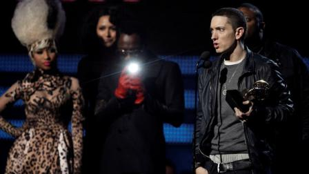 Eminem, right, accepts the award for best rap album, as Nicki Minaj and will.i.am look on at the 53rd annual Grammy Awards on Sunday, Feb. 13, 2011, in Los Angeles. (AP Photo/Matt Sayles)