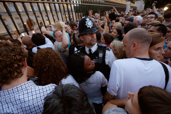 "<div class=""meta image-caption""><div class=""origin-logo origin-image ""><span></span></div><span class=""caption-text"">A police officer, center, tries to control a crowd of people trying to get to the railing to take pictures of a notice proclaiming the birth of a baby boy to Prince William and Kate, Duchess of Cambridge on display for public view at Buckingham Palace in London, Monday, July 22, 2013. (AP Photo/Sang Tan)    </span></div>"