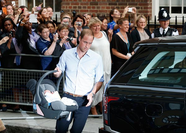 Britain's Prince William carries his son the Prince of Cambridge into a car outside St. Mary's Hospital exclusive Lindo Wing in London, Tuesday July 23, 2013 where his wife, Kate, the Duchess gave birth on Monday July 22. The Royal couple are expected to head to London's Kensington Palace from the hospital with their newly born son, the third in line to the British throne. (AP Photo/Lefteris Pitarakis)