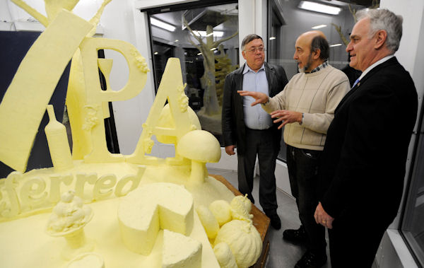Artist Jim Victor, center, talks about the 2013 butter sculpture with dairy farmer Harold Shaulis, left and Pennsylvania Secretary of Agriculture George Greig, during the sculpture's unveiling the 97th Pennsylvania Farm Show Thursday, Jan. 3, 2013 in Harrisburg, Pa. The 1,000-pound tableau, featuring milk and dairy items, grapes and wine, Christmas trees, and fruits and vegetables, pays tribute to the state's home-grown agricultural products. (AP Photo/Bradley C Bower)