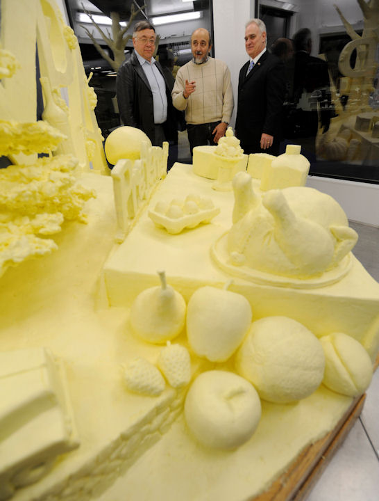 Artist Jim Victor, center, talks about the 2013 butter sculpture with dairy farmer Harold Shaulis, left and Pennsylvania Secretary of Agriculture George Greig, during the sculpture's unveiling at the 97th Pennsylvania Farm Show Thursday, Jan. 3, 2013 in Harrisburg, Pa. The 1,000-pound tableau, featuring milk and dairy items, grapes and wine, Christmas trees, and fruits and vegetables, pays tribute to the state's home-grown agricultural products. (AP Photo/Bradley C Bower)