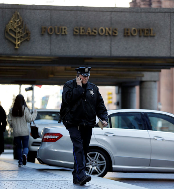 A police officer walks from the Four Seasons Hotel, Tuesday, Jan. 8, 2013, in Philadelphia. Philadelphia police are investigating a possible sexual assault at the upscale hotel, and the Brooklyn Nets say the probe involves one of the team's players. (AP Photo/Matt Rourke)