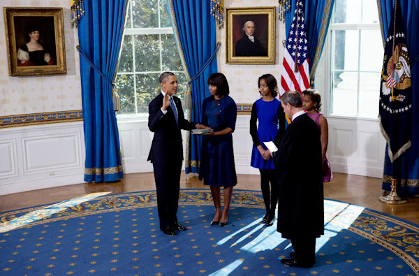 President Obama takes the oath of office at the official swearing-in ceremony in the Blue Room of the White House Sunday, Jan. 20, 2013. Administering the oath is Supreme Court Chief Justice Roberts. Holding the Bible is first lady Michele Obama and looking on are Obama children Sasha and Malia. (AP Photo/The New York Times, Doug Mills, Pool)