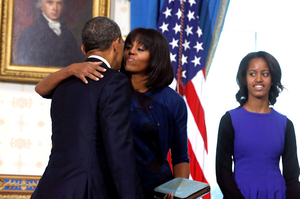 President Barack Obama gets a kiss from first lady Michelle Obama as daughter Malia watches after Obama was officially sworn-in by Chief Justice John Roberts, not pictured, in the Blue Room of the White House during the 57th Presidential Inauguration in Washington, Sunday, Jan. 20, 2013. (AP Photo/Larry Downing, Pool)