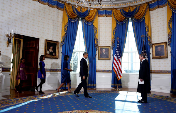President Barack Obama arrives to be officially sworn-in by Chief Justice John Roberts in the Blue Room of the White House during the 57th Presidential Inauguration in Washington, Sunday, Jan. 20, 2013. Following after him are first lady Michelle Obama, with the Robinson Family Bible, and daughters Malia and Sasha, right. (AP Photo/Larry Downing, Pool)