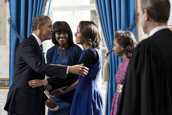 President Barack Obama embraces daughter Malia as first lady Michelle Obama and daughter Sasha, right, and Supreme Court Chief Justice John Roberts, Jr., look on after the official swearing-in in the Blue Room of the White House, Sunday, January 20, 2013 in Washington. (AP Photo/Brendan Smialowski, Pool)