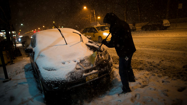 A motorist clears snow from his car on 59th Street, Friday, Feb. 8, 2013, in New York. Snow began falling across the Northeast on Friday, ushering in what was predicted to be a huge, possibly historic blizzard and sending residents scurrying to stock up on food and gas up their cars. &#40;AP Photo&#47;John Minchillo&#41;   <span class=meta>(AP Photo&#47;John Minchillo)</span>