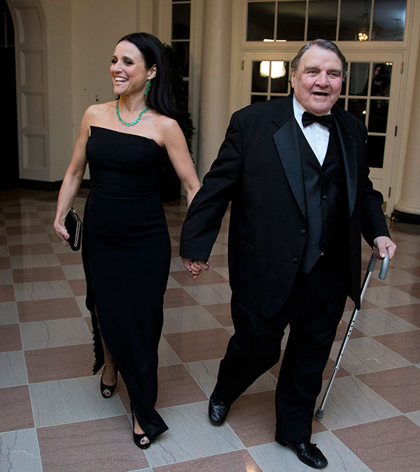 Actress Julia Louis-Dreyfus, left, arrives for a State Dinner in honor of French President Fran?ois Hollande with William Louis-Dreyfus at the White House in Washington, Tuesday, Feb. 11, 2014. (AP Photo/Manuel Balce Ceneta)