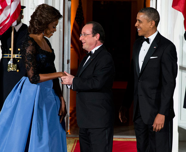 First lady Michelle Obama, left, and President Barack Obama welcome French President Fran?ois Hollande for a State Dinner at the North Portico of the White House on Tuesday, Feb. 11, 2014, in Washington. (AP Photo/ Evan Vucci)