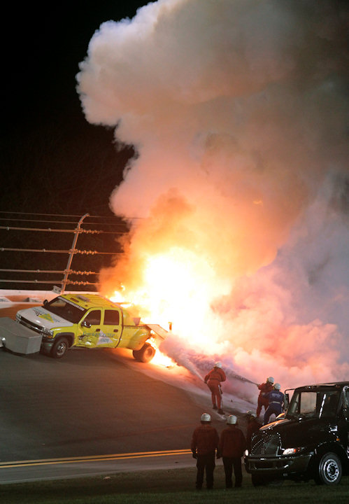 Emergency workers try to put out a fire on a jet dryer during the NASCAR Daytona 500 auto race at Daytona International Speedway in Daytona Beach, Fla., Monday, Feb. 27, 2012. (AP Photo/Bill Friel)