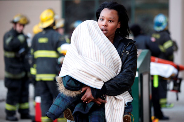 A woman and child evacuate a Philadelphia Housing Authority building after an early-morning fire, in Philadelphia, Wednesday, March 2, 2011.  (AP Photo/Matt Rourke)