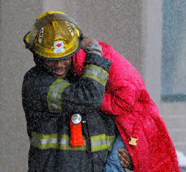 A firefighter evacuates a child from a Philadelphia Housing Authority building after an early-morning fire in Philadelphia, Wednesday, March 2, 2011. (AP Photo/Matt Rourke)