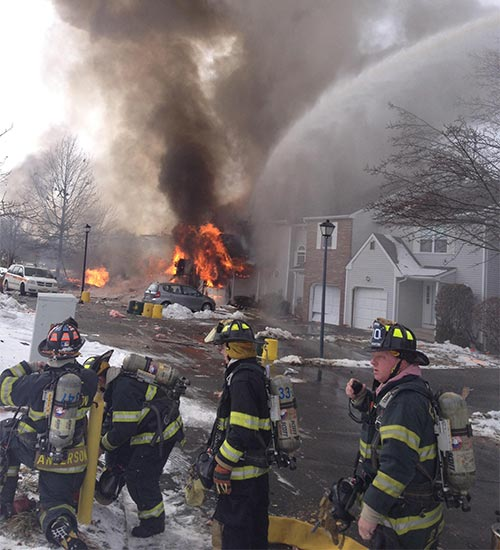 A viewer-submitted photos shows firefighters responding as flames roar in the background after at least one house exploded in Ewing Township, New Jersey early Tuesday afternoon.