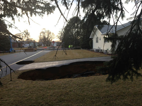 A massive sinkhole, at least 30 feet wide and...