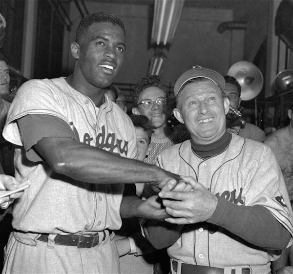 Jackie Robinson, left, Brooklyn Dodgers' second baseman who slammed out a homer in the 14th inning to beat the Phillies 9-8 at Shibe Park in Philadelphia, September 30, 1951, gets the congratulations of manager Charley Dressen after the game. (AP Photo)